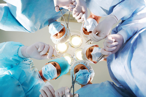 surgeons looking down while operating